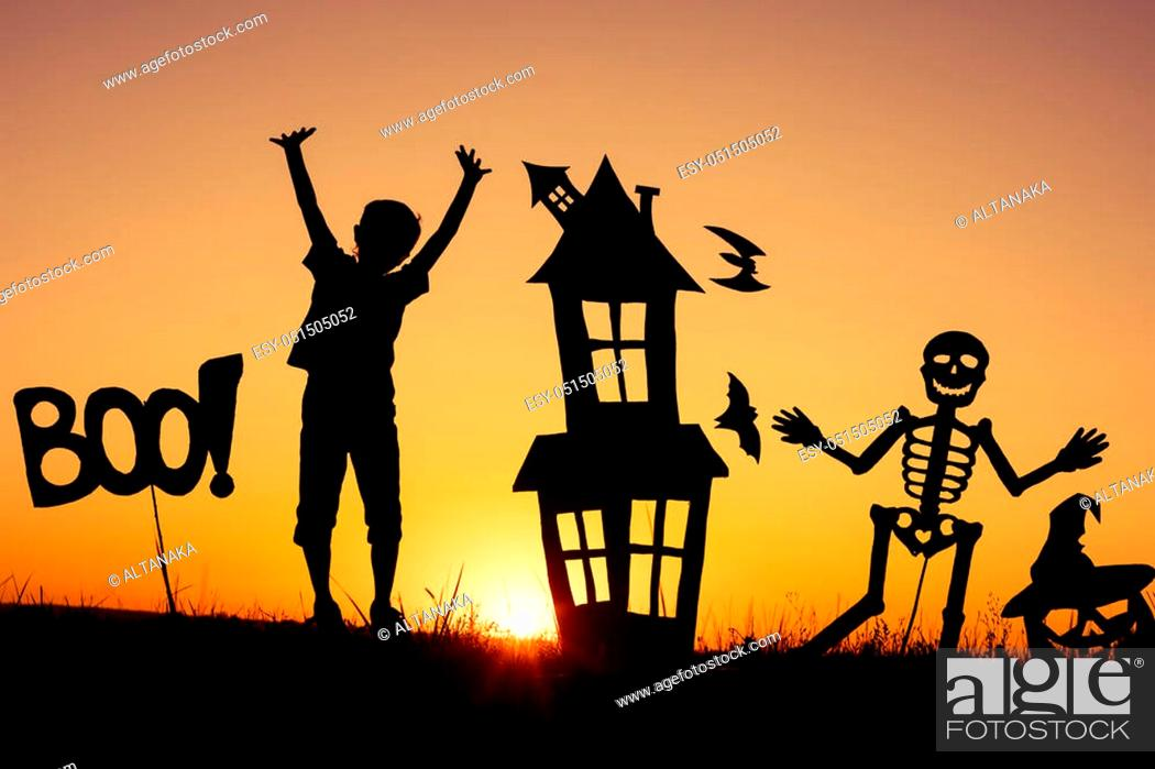 Stock Photo: Happy little boy playing outdoors at the sunset time. Kid having fun. Concept of happy Halloween party.