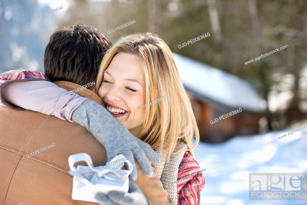 Stock Photo: Smiling woman holding Christmas gift and hugging man in snowy field.