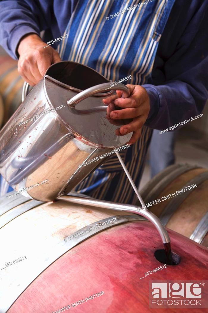 Stock Photo: Topping off Wine Barrel After Refilling.
