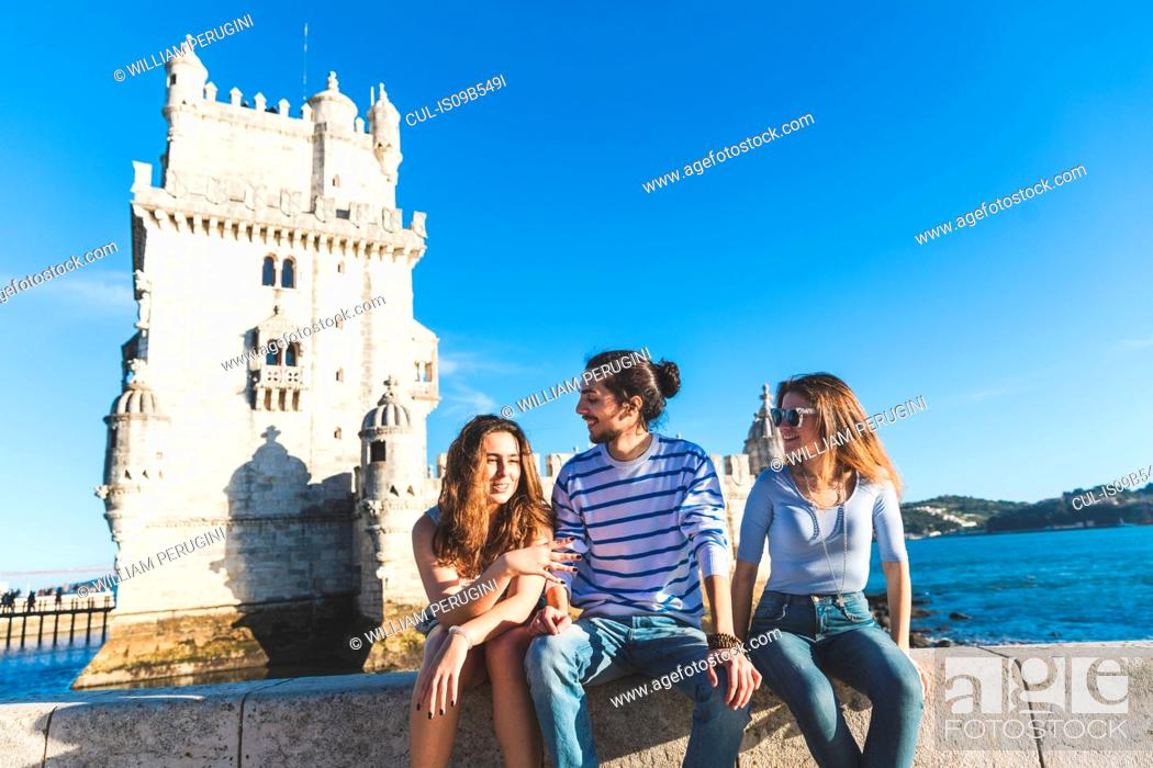 Stock Photo: Three friends, sitting on wall by sea, Belem Tower in background, Lisbon, Portugal.