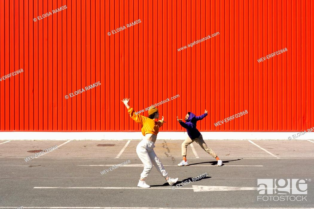 Stock Photo: Young man and woman performing in front of a red wall.
