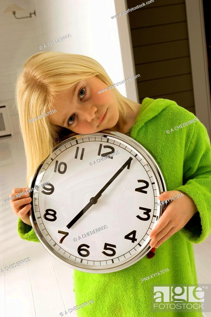 Stock Photo: Portrait of a girl holding a clock.