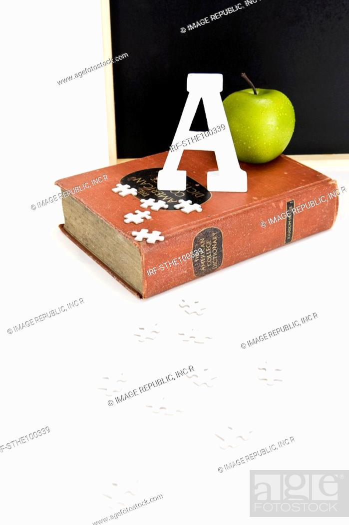 Stock Photo: apple, A and dictionary in front of blackboard.