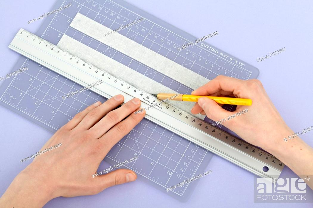 Imagen: Cutting masking tape to size to create stencil for picture frame.