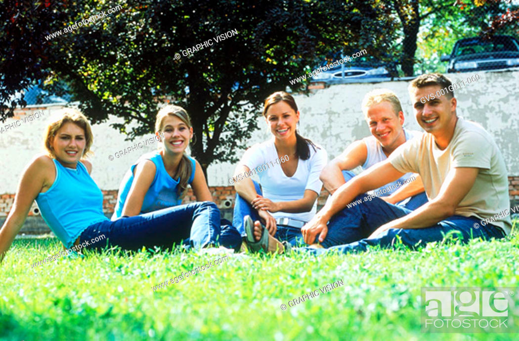Stock Photo: A group of young people sitting together on a lawn.