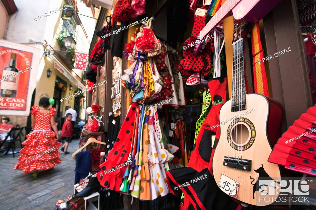 Stock Photo: Girl in traditional Seville dress passing shop selling souvenirs in old town; Santa Cruz, Seville, Andalucia, Spain.