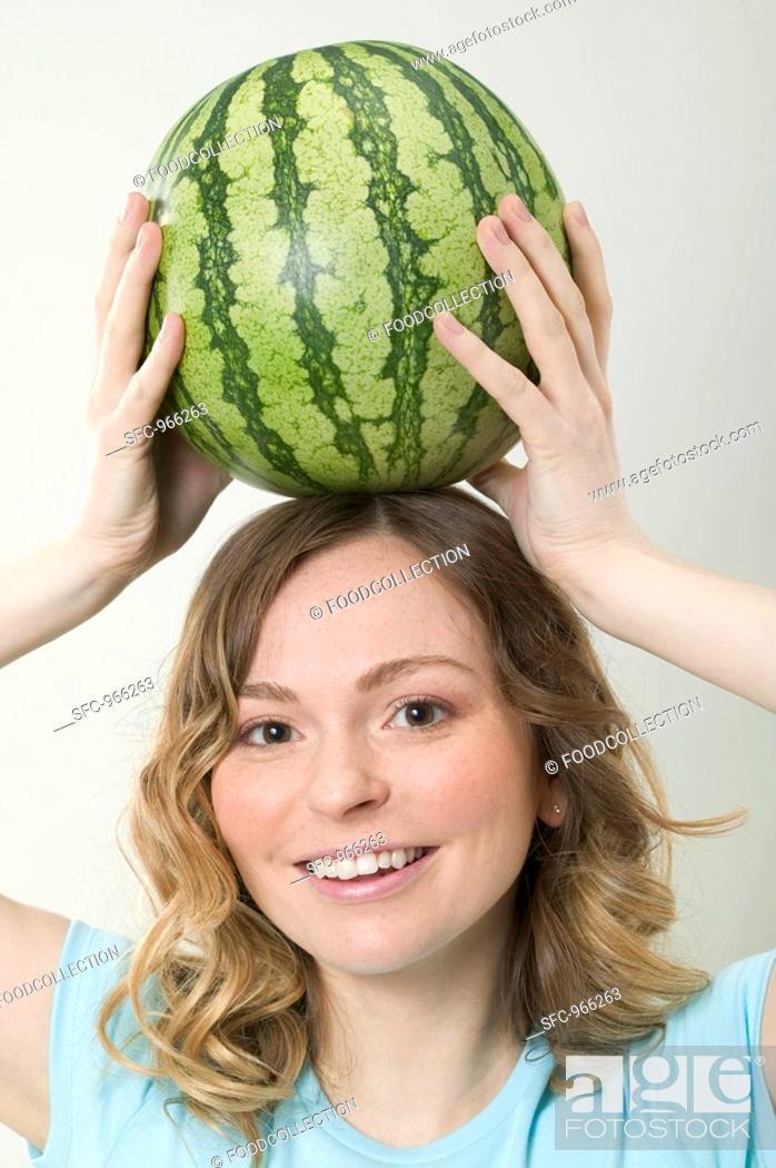 Stock Photo: Woman balancing watermelon on her head.
