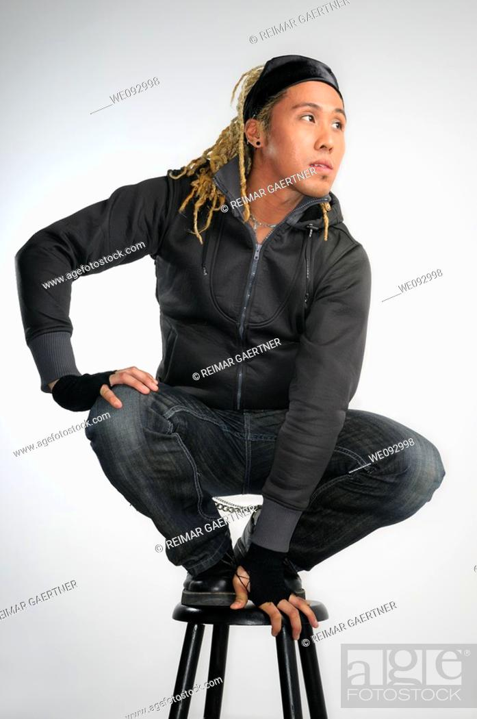 Stock Photo: Asian man with dreadlocks crouching on a stool.