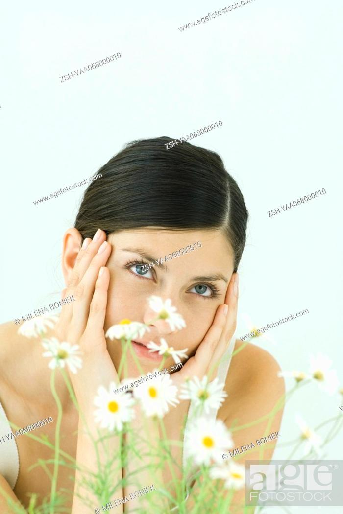 Stock Photo: Woman behind chamomile plant, holding head, looking up.