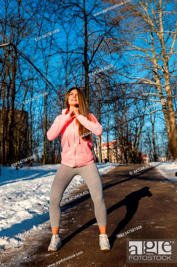 Stock Photo: Young girl goes in for sports in winter park. Squats are one of the General developmental exercises.