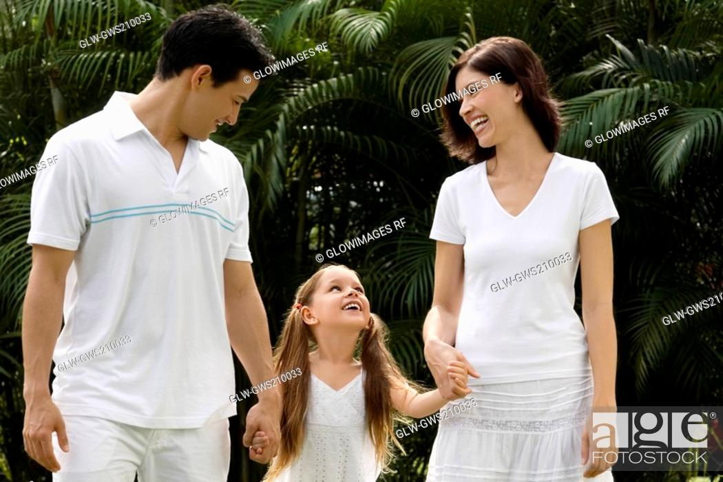 Stock Photo: Young couple walking with their daughter in a garden and smiling.