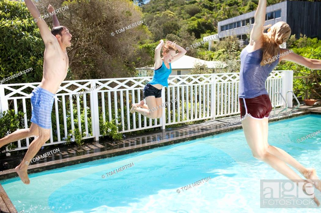 Stock Photo: Friends jumping into swimming pool.