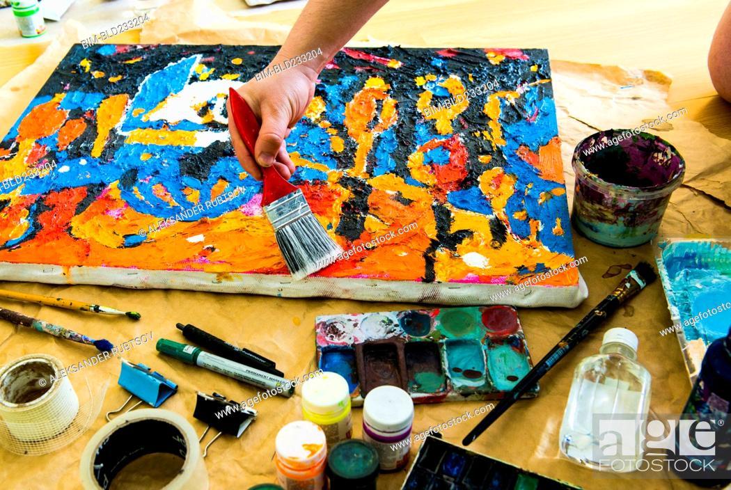 Stock Photo: Hand brushing paintbrush over canvas painting.