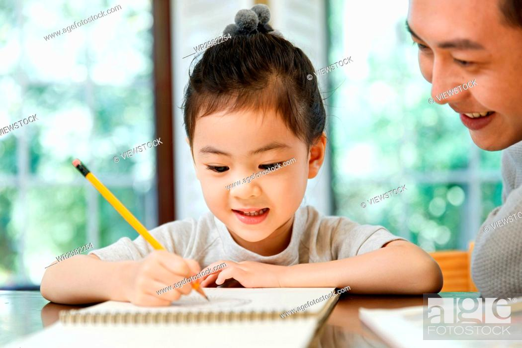 Stock Photo: Father helping daughter with her study.
