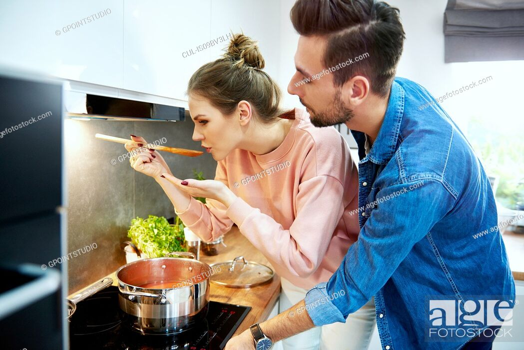 Stock Photo: Couple tasting tomato soup in kitchen.
