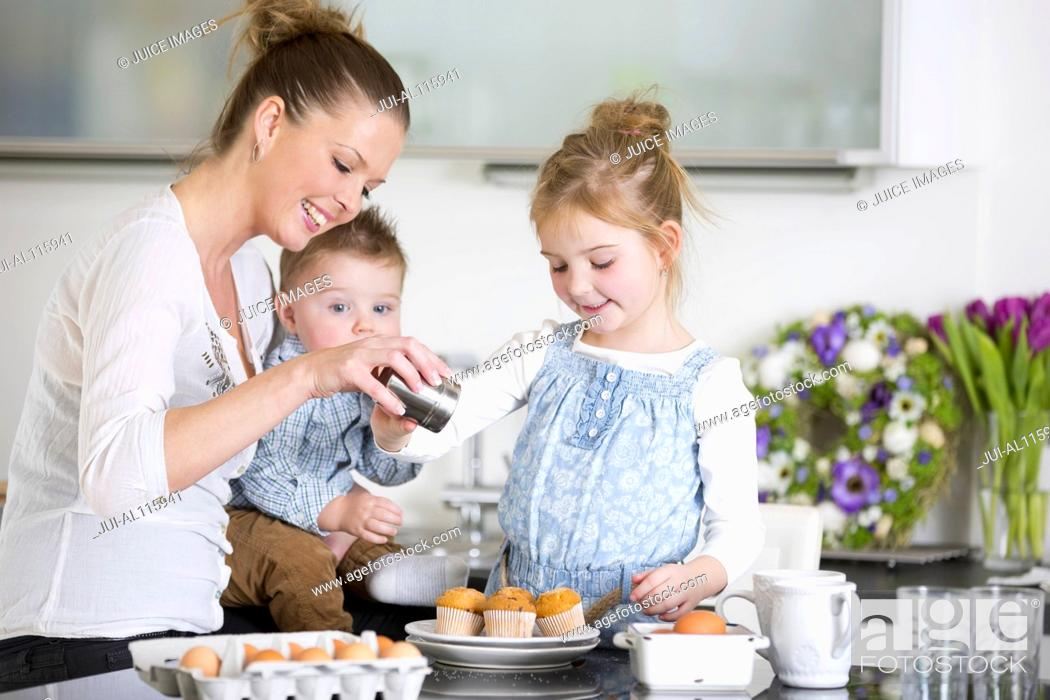 Stock Photo: Mother and family with cupcakes in kitchen.