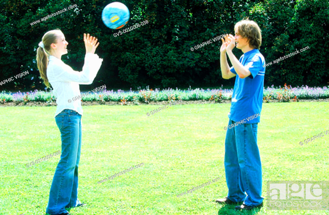 Stock Photo: Young couple playing with a ball in a garden.
