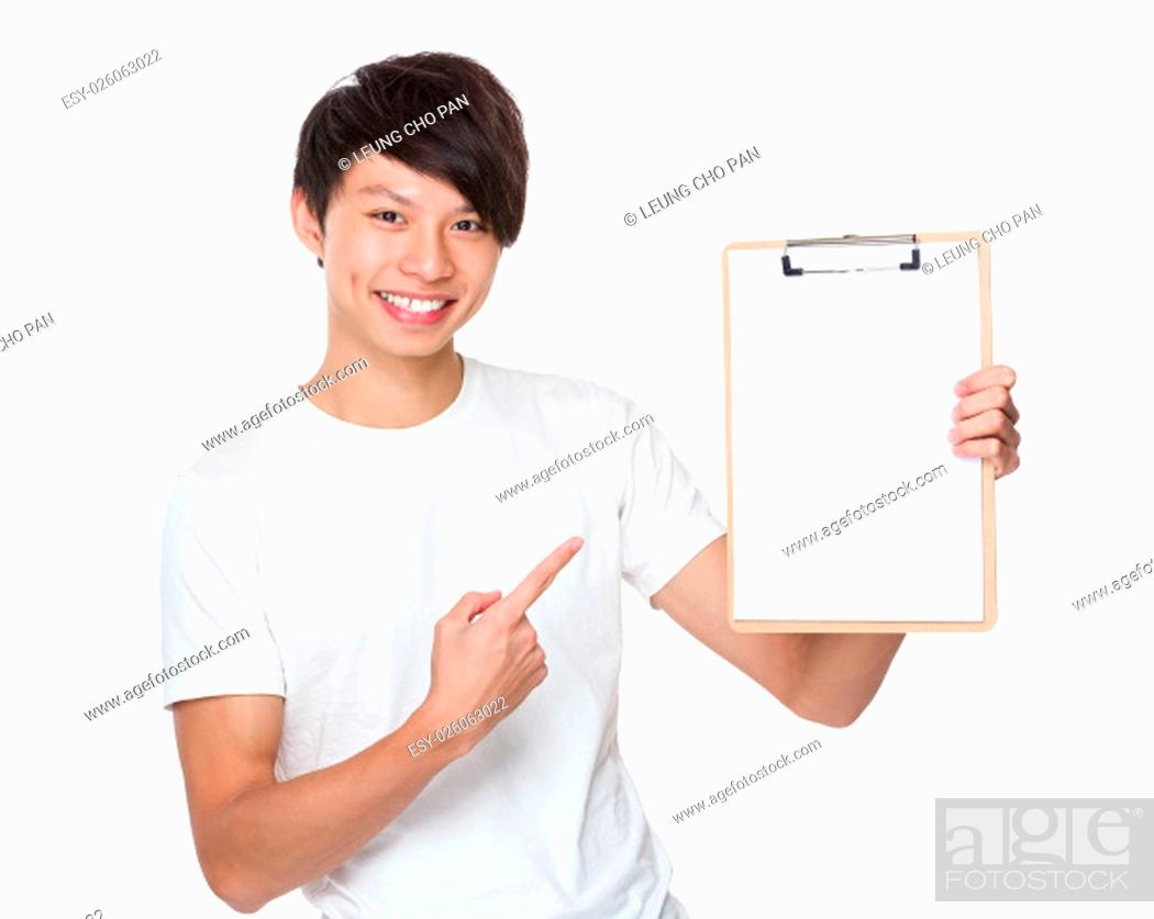 Stock Photo: Asian young man finger point to blank page of clipboard.