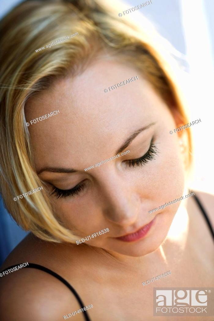 Stock Photo: Caucasian mid-adult blonde woman looking down.