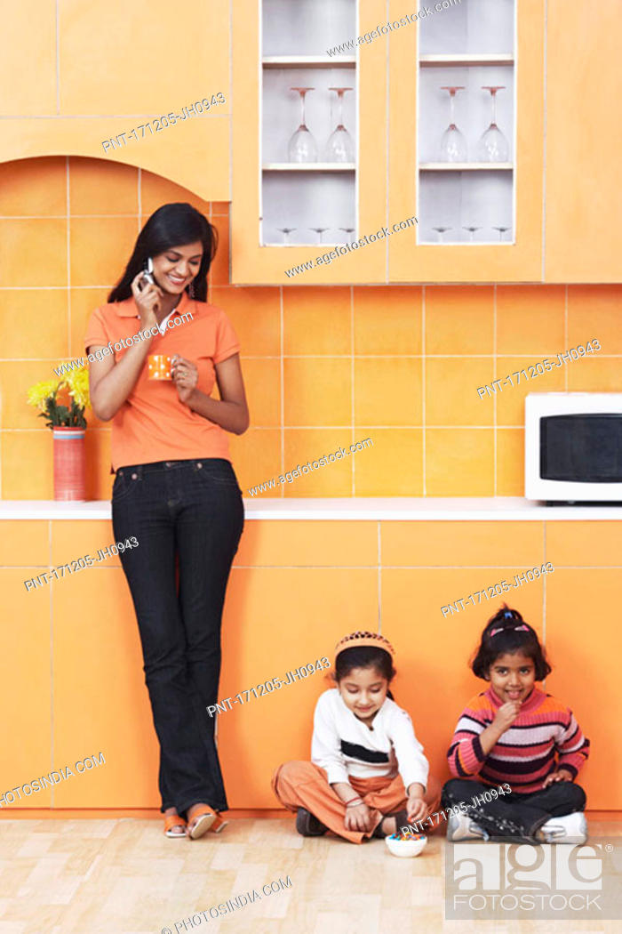 Stock Photo: Mother talking on a mobile phone with her daughters sitting on the floor.