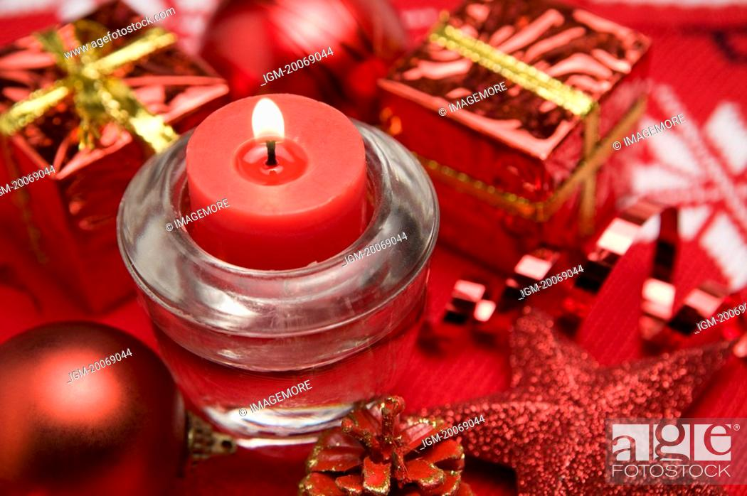 Stock Photo: Gift around a lit candle.