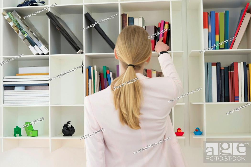 Stock Photo: Woman taking out a book from shelf.