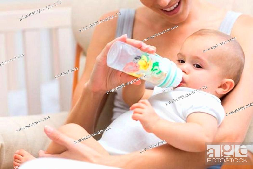 Stock Photo: Mother feeding baby with milk bottle.