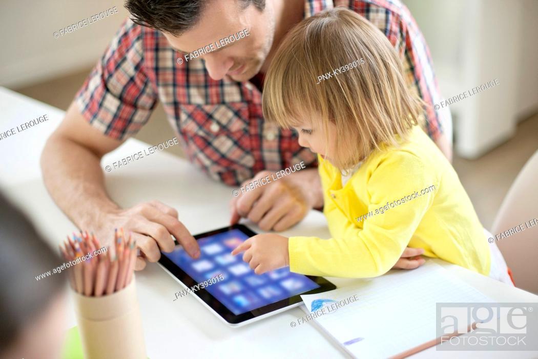 Stock Photo: Man teaching digital tablet to his daughter.