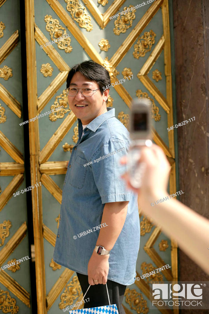 Stock Photo: Female hand taking a picture of an Asian man who is standing in front of an ornate door, selective focus.
