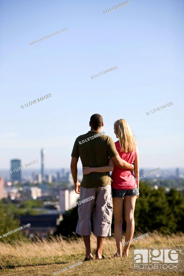 Stock Photo: A young couple in a park, looking across the city.