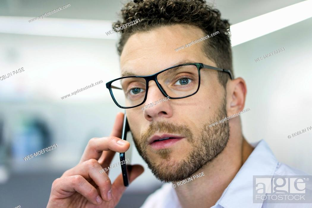 Stock Photo: Portrait of businessman on cell phone in office.