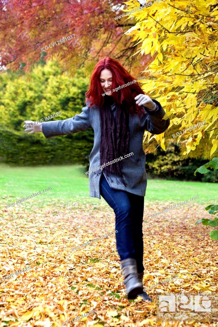 Stock Photo: A young woman kicking leaves in autumn time.