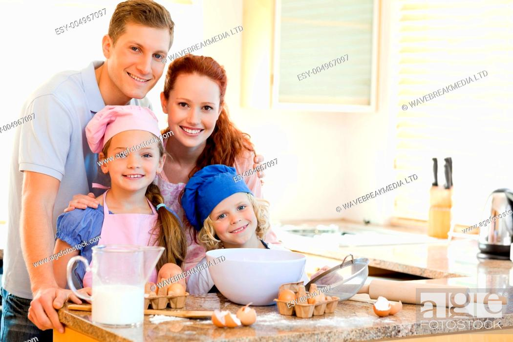 Stock Photo: Family with baking ingredients behind the kitchen counter.