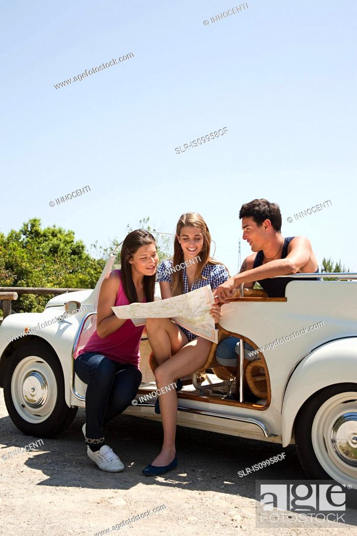 Stock Photo: Young friends with convertible car looking at map.