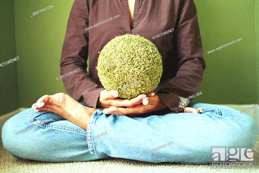 Stock Photo: Woman sitting with astroturf ball.