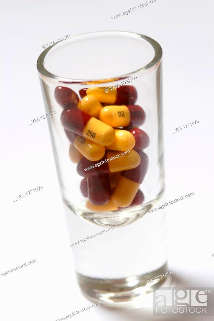 Stock Photo: Medicine tablets and pills in shot glass close up.