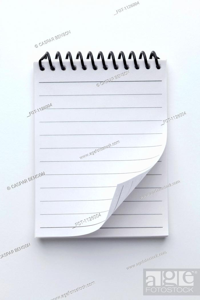 Stock Photo: A spiral notepad with lined paper and a curled up page corner.