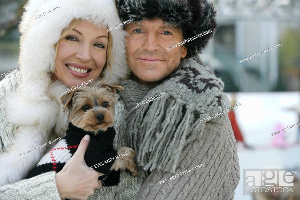 Stock Photo: Mature couple holding a Yorkshire Terrier.