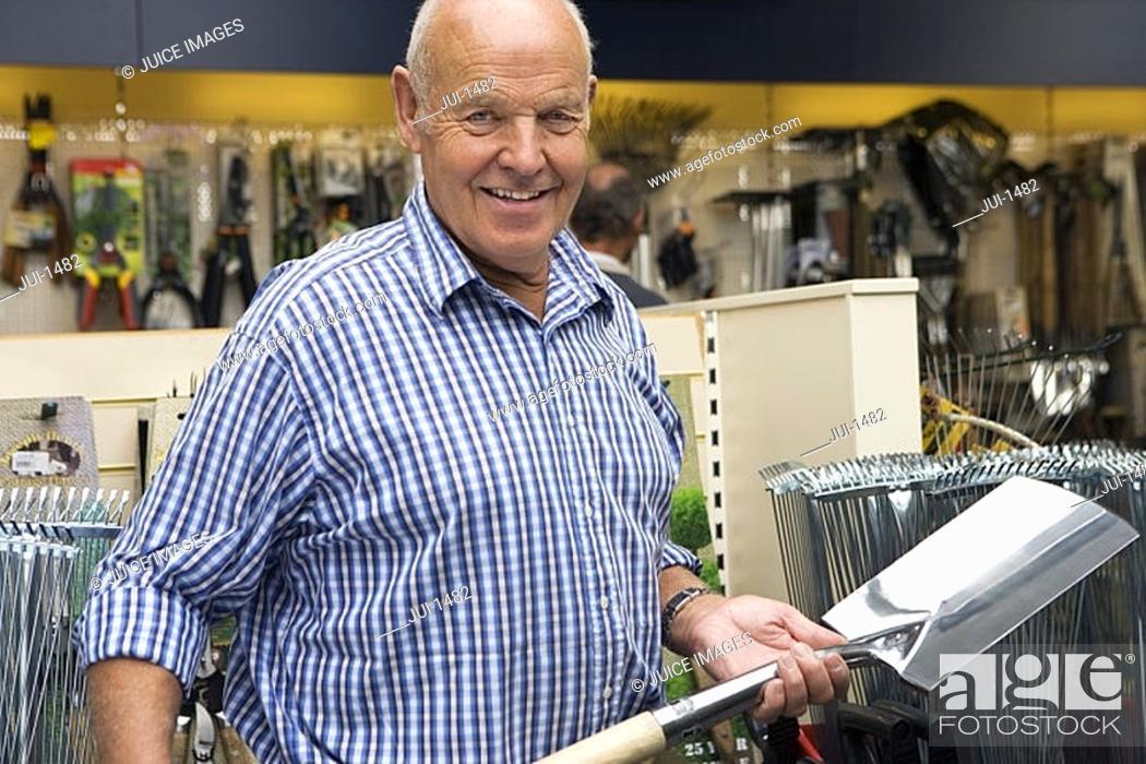 Stock Photo: Senior man shopping in garden centre, holding new spade, smiling, portrait.