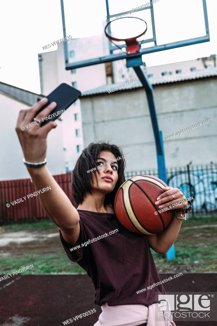 bef15f1968c8 Stock Photo - Young woman with basketball taking a selfie on outdoor court