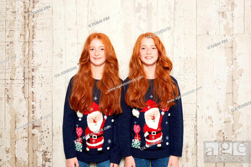 Stock Photo: Portrait of twin sisters wearing Christmas jumpers.