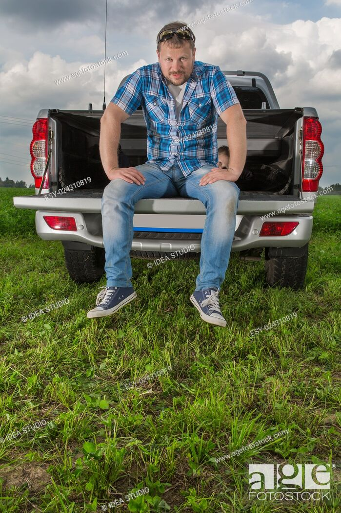 Stock Photo: Solid man sitting on car trunk on natural background.