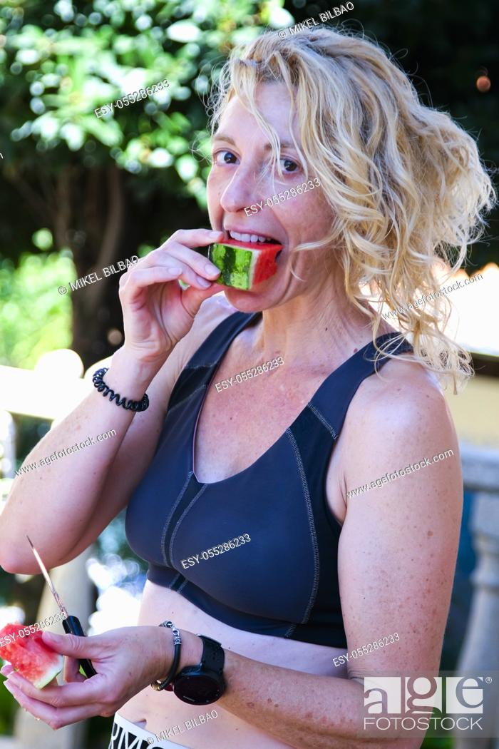 Stock Photo: Young mature blonde woman in sportswear eating melon outdoor.