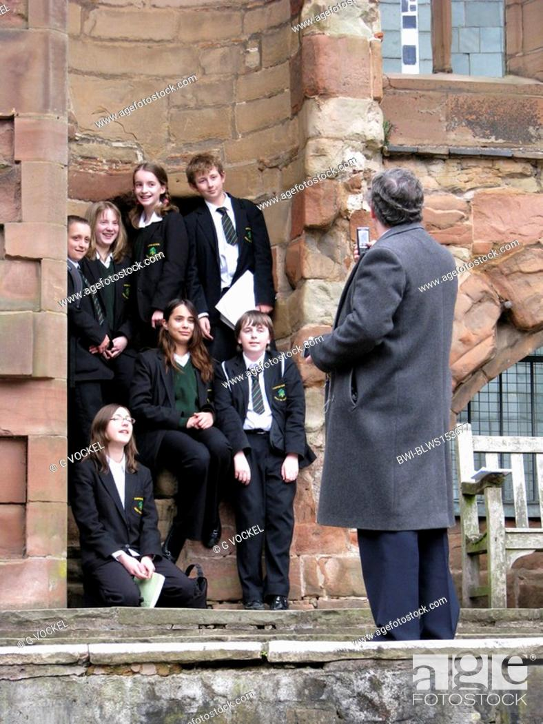Stock Photo: teacher taking a picture of a group of pupils in the ruins of the Cathedral of Coventry, United Kingdom, England, Coventry.