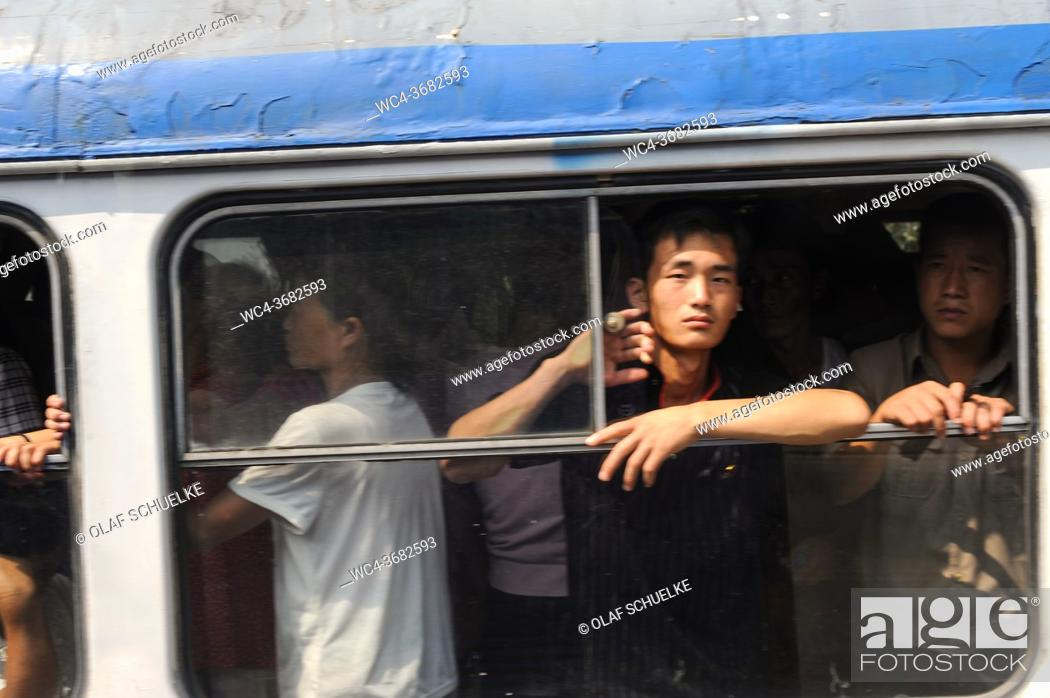 Stock Photo: Pyongyang, North Korea, Asia - Commuters look out of an open window of a fuly occupied tram in the centre of the North Korean capital city.