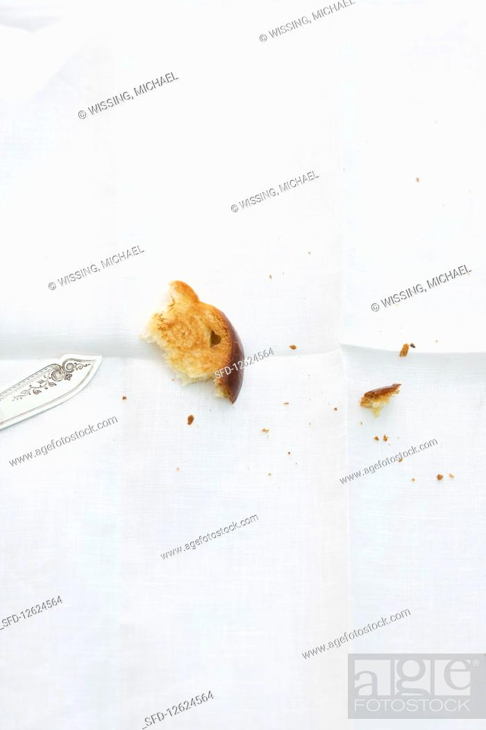 Photo de stock: A piece of brioche and crumbs on a white tablecloth.