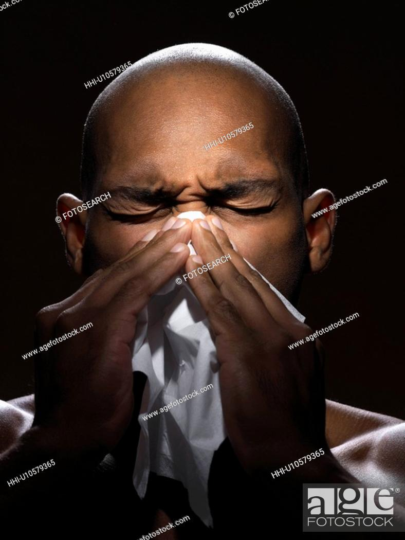 Stock Photo: Young man blowing nose.