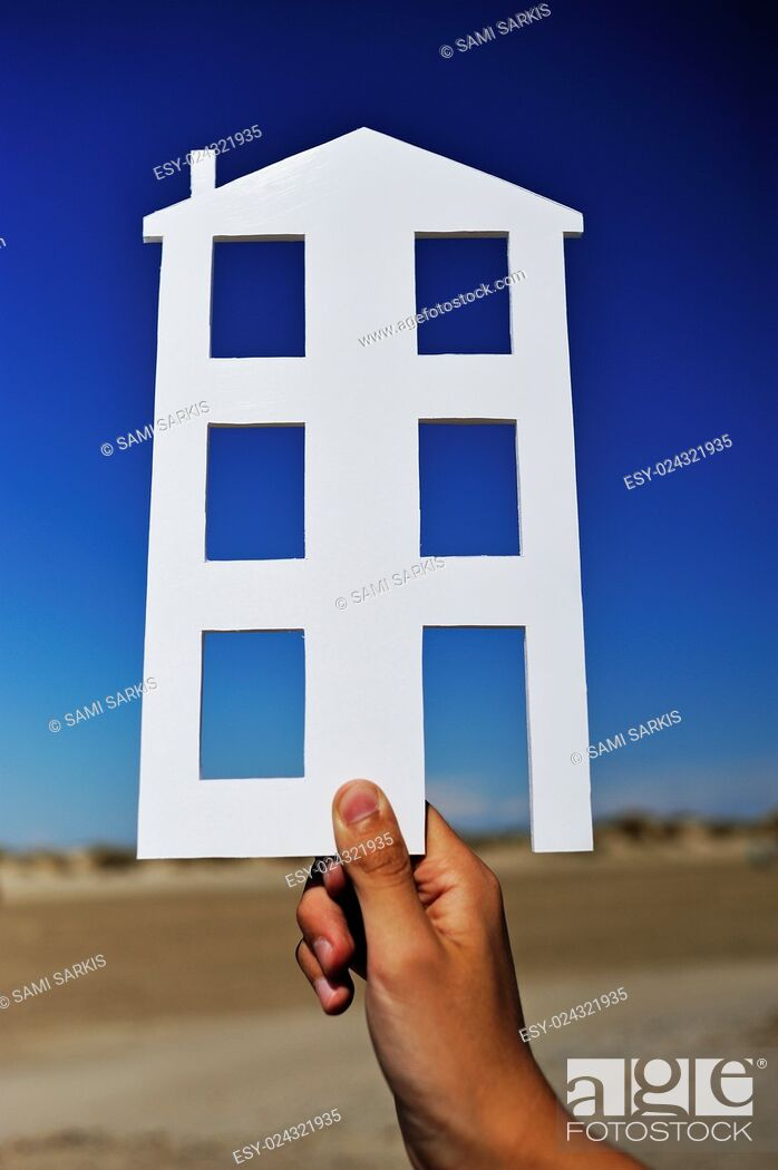 Imagen: Hand holding house shape on an empty plot of land - design, construction, new homes concept.