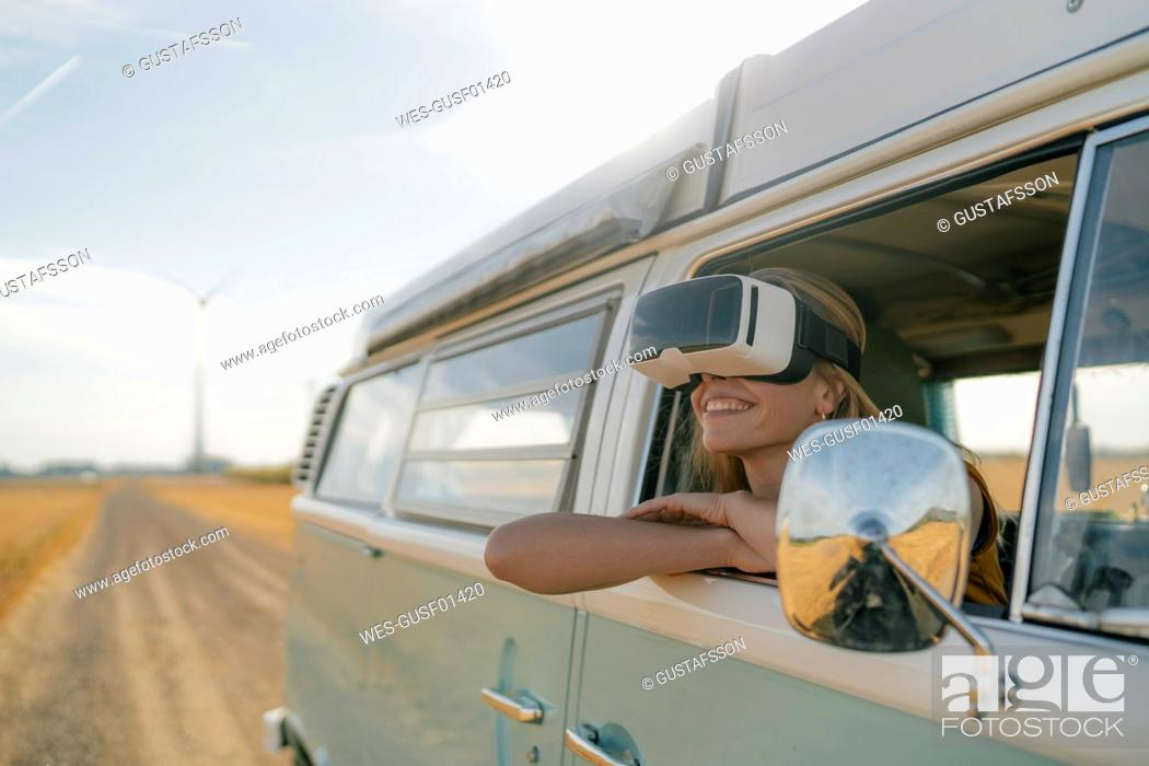 Stock Photo: Smiling woman wearing VR glasses leaning out of window of a camper van.