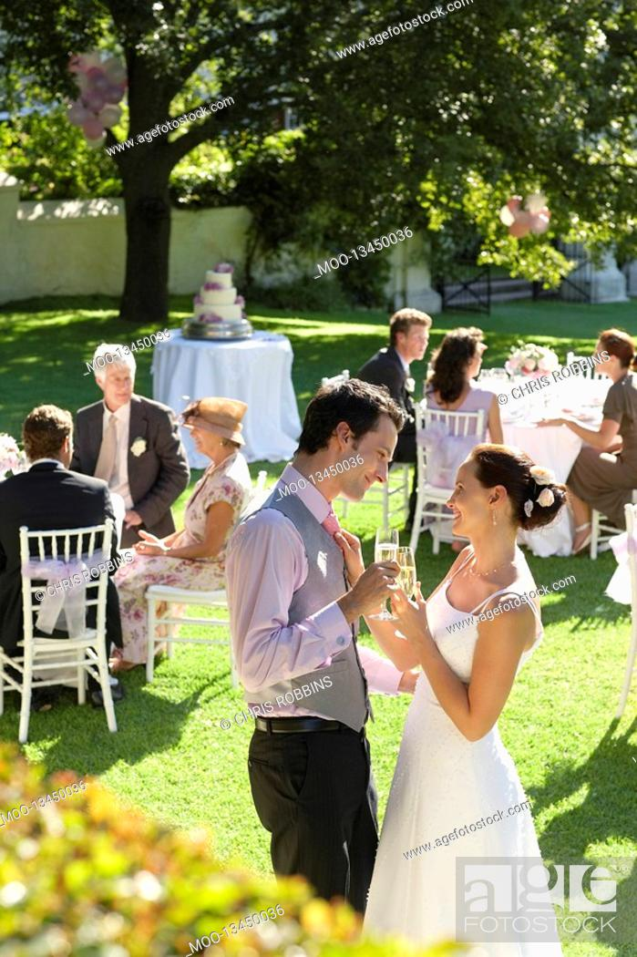 Stock Photo: Mid adult bride and groom in garden toasting among wedding guests.